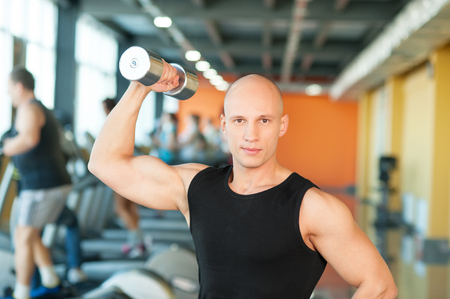 Young man training with dumbbells at the gym photo