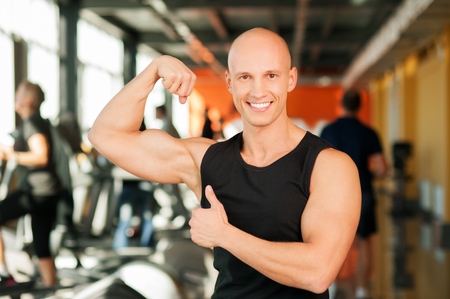 Smiling man standing and showing his muscles photo