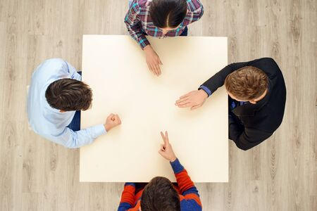 scissors: Top view of table with group of creative people playing rock paper scissors game