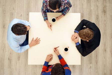 personas sentadas: Vista desde arriba de la mesa con un grupo de j�venes creativos ocupados que trabajan en proyecto. Concepto de equipo de negocios Foto de archivo