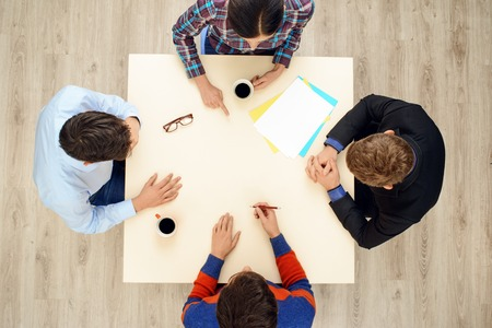 aucasian: Top view of table with group of busy people working on project. Business team concept