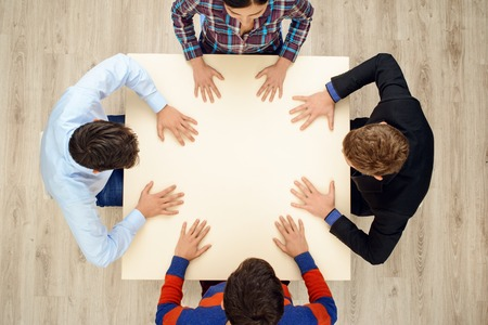 aucasian: Top view of table with group of creative people working on project. People sitting with their hands on table