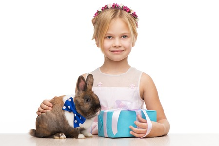 aucasian: Little girl and brown bunny with blue bow tie sitting near blue present box. Concept for holidays Stock Photo