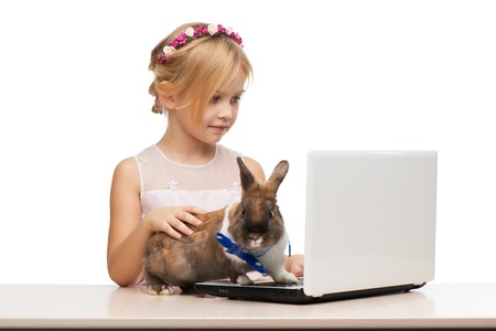 �aucasian: Little girl and brown bunny working on the computer, isolated on white Stock Photo