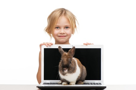 aucasian: Cute girl looking out of a laptop where little bunny is sitting, isolated on white background