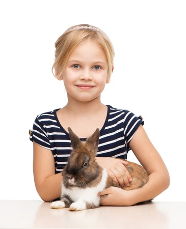 aucasian: Little beautiful girl looking at camera and holding brown bunny, isolated on white Stock Photo