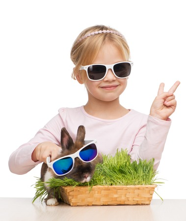 aucasian: Photo of little smiling girl showing victory sign and brown bunny in sunglasses, isolated on white Stock Photo