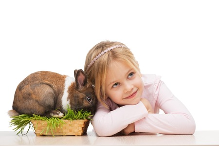 aucasian: Little girl is isolated on white background with cute brown bunny in grass