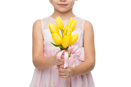 �aucasian: Close up picture of cute girl wearing pink dress, standing isolated on white background and holding nice bouquet of yellow tulips