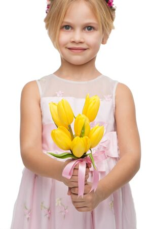 aucasian: Close up photo of cute girl wearing pink dress, standing isolated on white background and holding nice bouquet of yellow tulips
