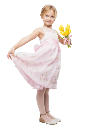 aucasian: Little girl wearing pink dress, standing isolated on white background and holding nice bouquet of yellow tulips Stock Photo