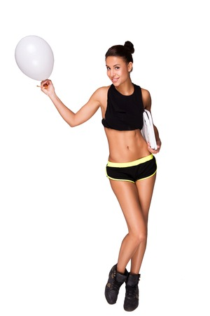 weighs: Young mixed race sporty woman holding white balloon and weighs, standing on grey background Stock Photo