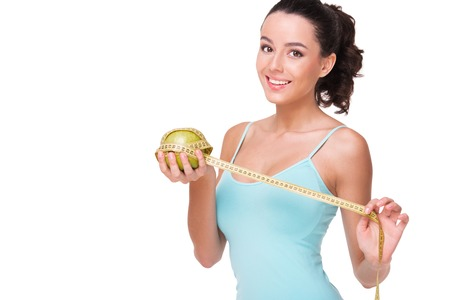 aucasian: Young fit woman measuring apple with tape, isolated on white background. Concept for health and beauty