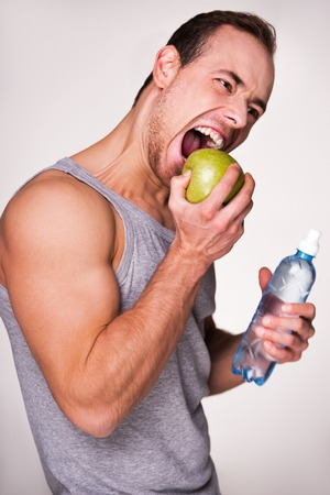aucasian: Young sporty man biting an apple and holding a bottle of water, standing on grey background