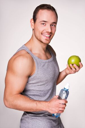 �aucasian: Young sporty man holding a bottle of water and an apple, standing on grey background Stock Photo