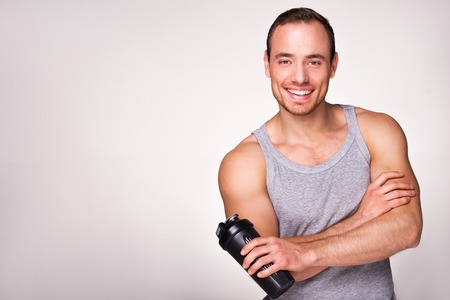 aucasian: Young sporty man holding black sport shaker, standing on grey background