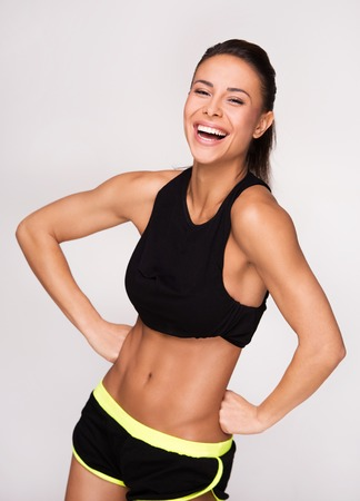 Cheerfully smiling mixed race sporty woman looking at camera, isolated on white background Stock Photo