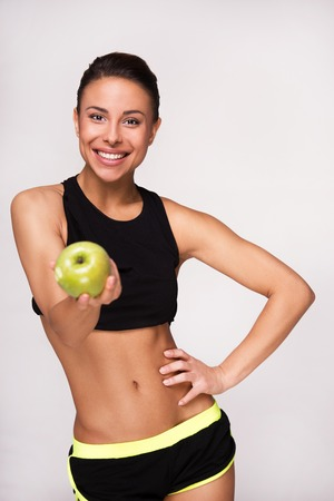 Sorridente gara sportiva donna mixed che mostra mela verde alla macchina fotografica, isolato su sfondo bianco Archivio Fotografico - 36944799