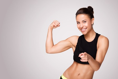 Cheerfully smiling mixed race sporty woman demonstrating biceps, isolated on white background