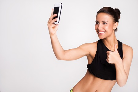 tumb: Young mixed race sporty woman making selfie with thumb up, standing on grey background Stock Photo