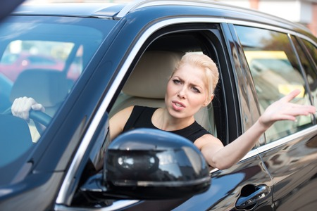 Unhappy and nervous young woman while driving in traffic jam