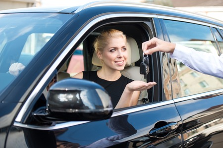 new motor car: Young smiling woman getting keys of a new car. Concept for car rental