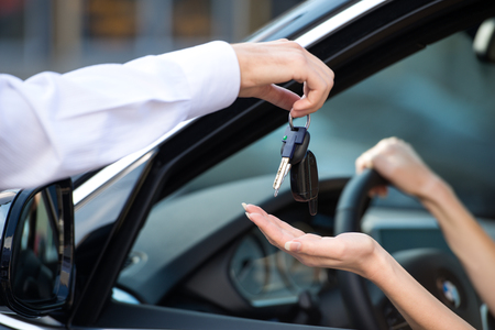 key ideas: Close up of car dealer giving keys of a new car to woman. Concept for car rental Stock Photo