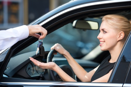 Car dealer giving keys of a new car to happy smiling woman. Concept for car rental