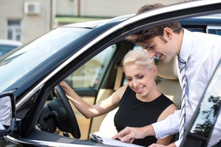 Autohändler und glücklich lächelnde Frau Unterzeichnung eines Vertrages. Konzept für Autovermietung Standard-Bild