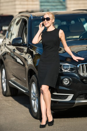 auto insurance: Young beautiful woman with sunglasses and phone leaned on her car. Concept for car rental
