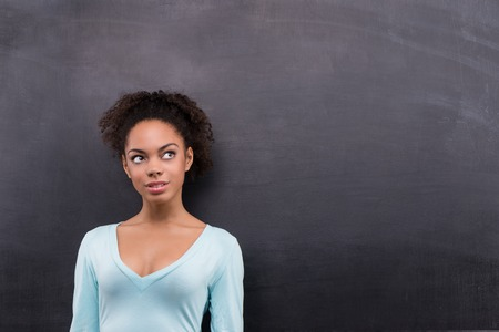 aside: Photo of beautiful young afro-american woman on blank chalkboard background. Woman smiling and looking aside
