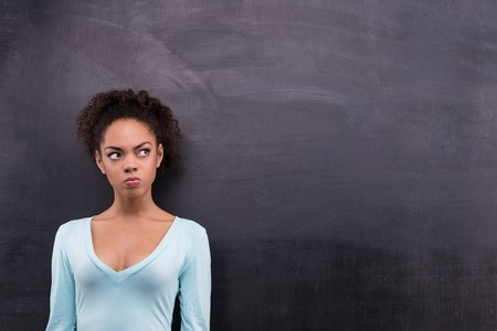 aside: Photo of young angry afro-american woman on blank chalkboard background. Woman looking aside