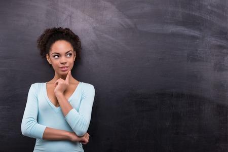 Foto van jonge Afro-Amerikaanse vrouw op lege bord achtergrond. Vrouw glimlacht en kijkt opzij