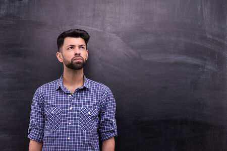 blank chalkboard: Photo of handsome young casual man on blank chalkboard background. Man looking aside