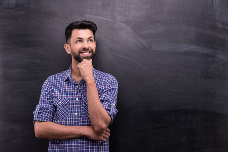 aside: Photo of handsome young casual man on blank chalkboard background. Man smiling and looking aside