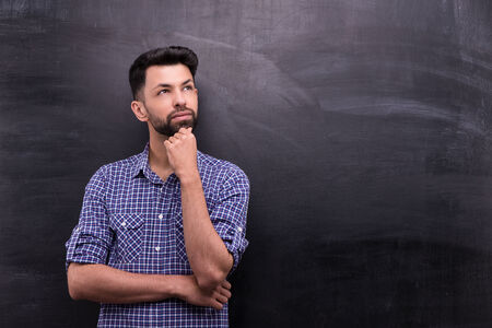 aside: Photo of handsome young casual man on blank chalkboard background. Man thoughtfully looking aside Stock Photo