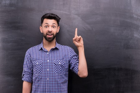 blank chalkboard: Photo of handsome young casual man on blank chalkboard background. Man excitedly pointing at something Stock Photo