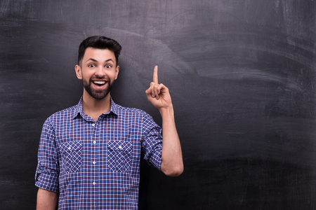 blank chalkboard: Photo of handsome young casual man on blank chalkboard background. Man smiling and cheerfully pointing at something Stock Photo