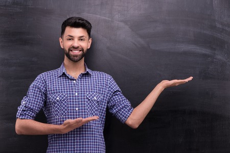 blank chalkboard: Photo of handsome young casual man on blank chalkboard background. Man smiling and cheerfully pointing at something with two hands