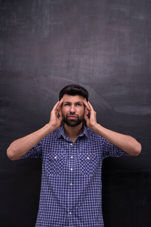 blank chalkboard: Photo of handsome young casual man on blank chalkboard background. Terrified man with headache