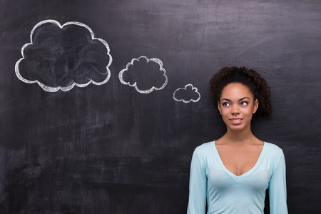 creative writing: Photo of smiling young afro-american woman on chalkboard background. Woman looking at cloud formed dialog
