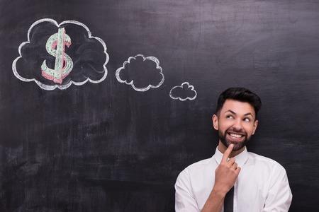 黒板背景にハンサムな青年実業家の写真。男の黒板に描いた雲がダイアログとそれにドル記号を見て元気 写真素材