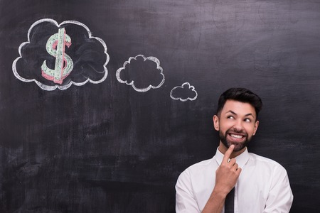 cheerfully: Photo of handsome young businessman on chalkboard background. Man cheerfully looking at cloud formed dialog and dollar sign in it painted on chalkboard