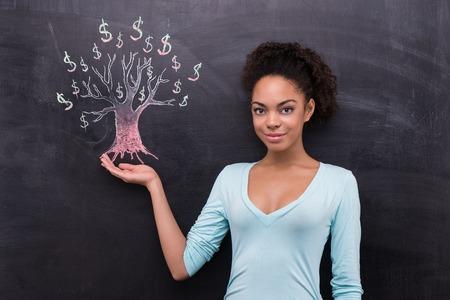 femme dessin: Photo de jeune femme afro-américaine sur fond tableau. Femme regardant la caméra. Dollar tree peint sur tableau noir