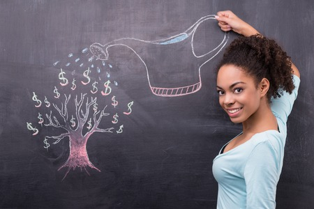 woman think: Photo of young afro-american woman on chalkboard background. Smiling woman looking at camera and watering dollar tree painted on chalkboard