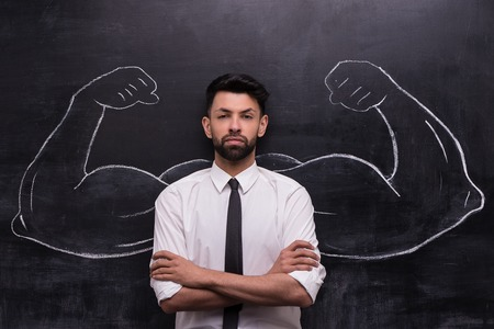 creative work: Funny picture of young businessman on chalkboard background seriously looking at camera. Two strong muscular arms painted on chalkboard Stock Photo