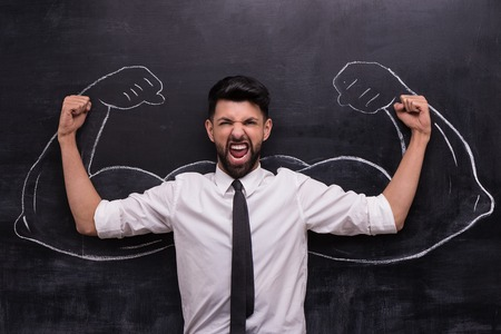 Funny picture of young businessman ready to win on chalkboard background. Two strong muscular arms painted on chalkboard