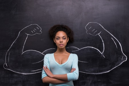 Funny picture of young afro-american woman on chalkboard background seriously looking at camera. Two strong muscular arms painted on chalkboard