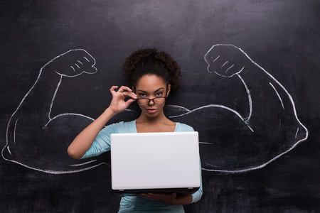 people development: Funny picture of young afro-american woman with laptop on chalkboard background. Two strong muscular arms painted on chalkboard