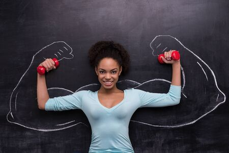 funny picture: Funny picture of smiling afro-american woman with dumbbells on chalkboard background. Two strong muscular arms painted on chalkboard Stock Photo
